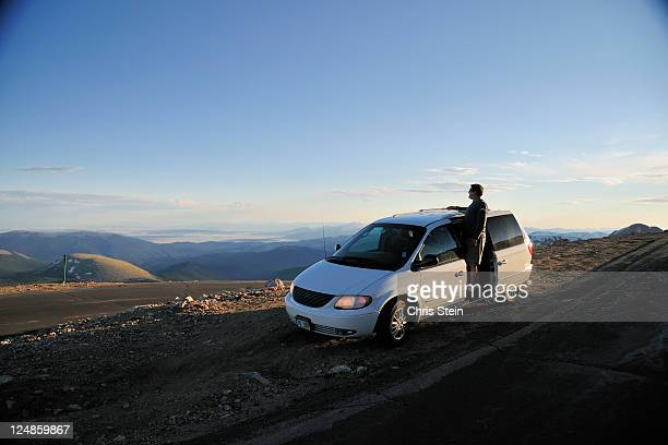 Man looking at the scenic view from his minivan