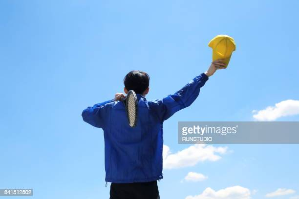 Man looking at the sky and holding tennis racket
