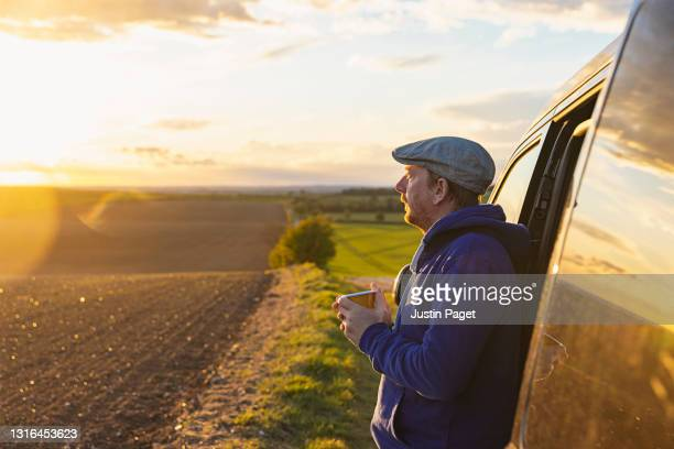 man looking at the view from her campervan - headwear stock pictures, royalty-free photos & images