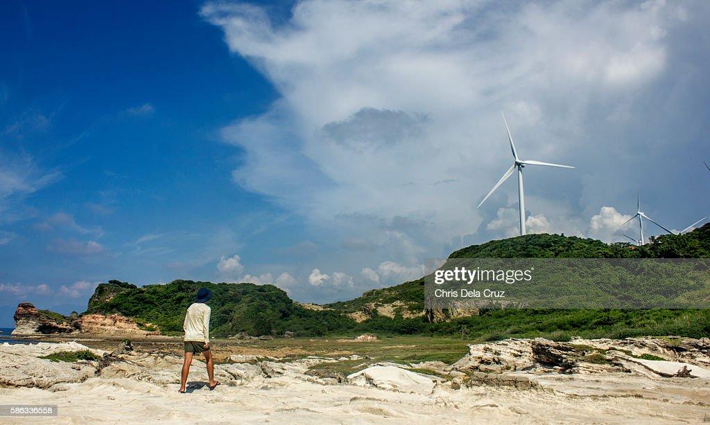 Man looking at the windmills at Kapurpurawan Rock Formation : Stock Photo