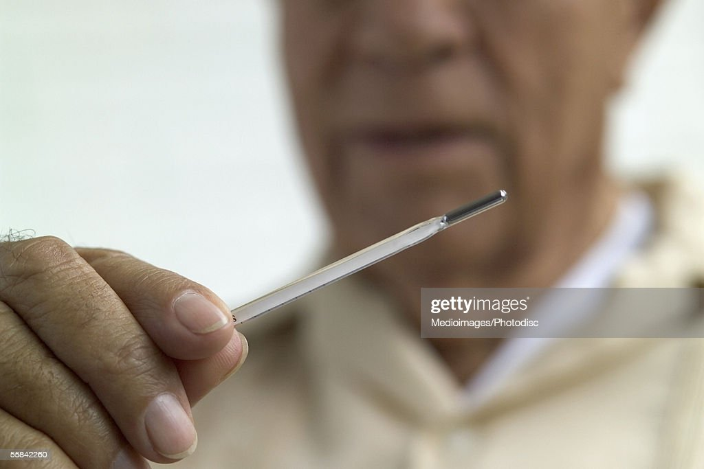 Man looking at thermometer, close-up, focus on hand and thermometer : Stock Photo