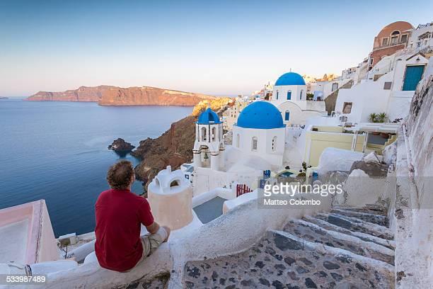 man looking at town of oia, santorini, greece - oia santorini foto e immagini stock