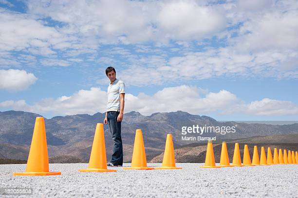 Man  looking at traffic cones in line outdoors ground level view