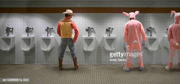 man looking at two men in rabbit costume at urinal, rear view (digital composite) - chelsea mask stock pictures, royalty-free photos & images