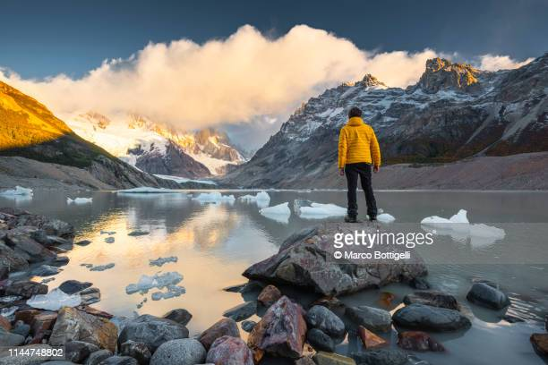 man looking at view at sunrise in los glaciers national park, argentina - avontuur stockfoto's en -beelden