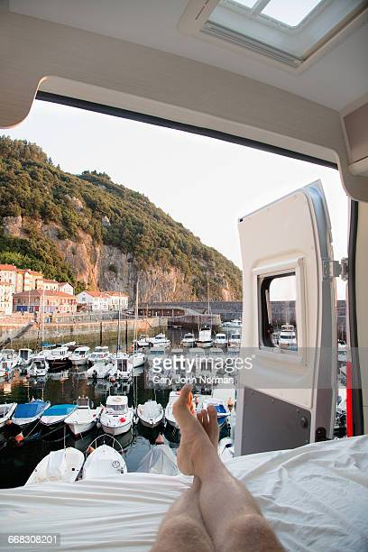 POV Man looking at view of boats from campervan