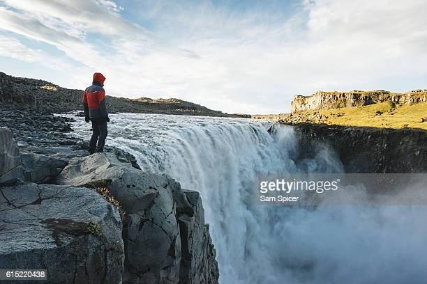 man looking at view of epic waterfall in iceland - dettifoss waterfall stock photos and pictures