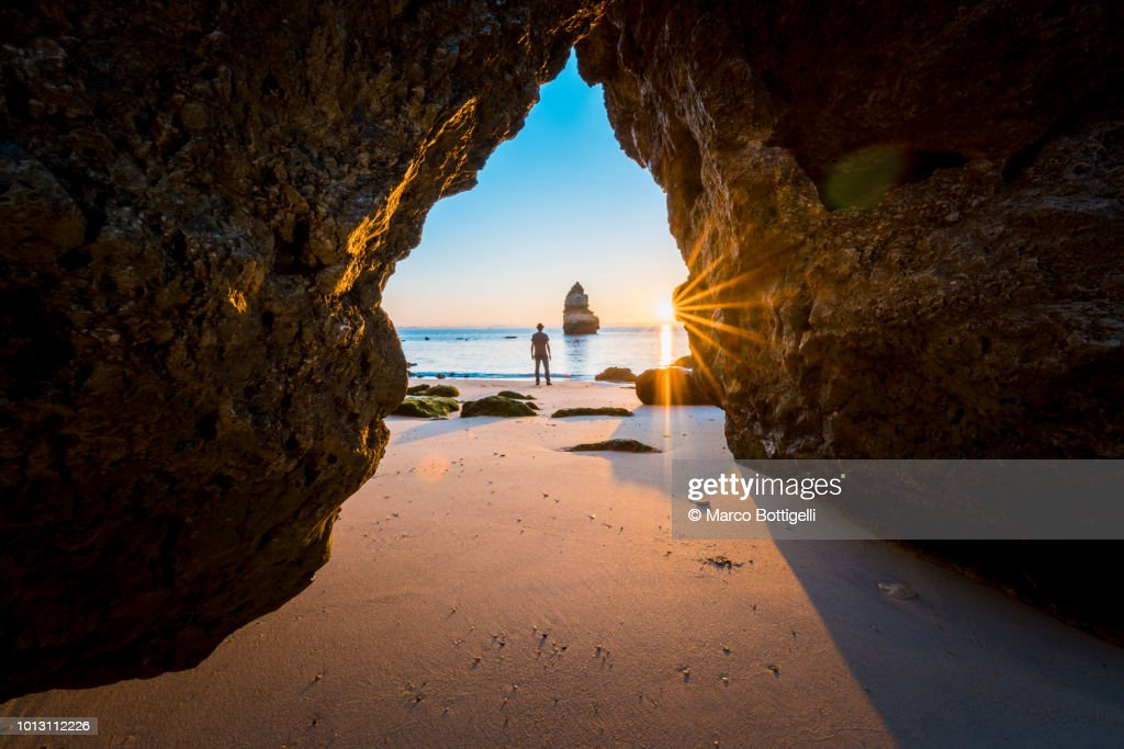 Man looking at view on the beach at sunrise, Algarve, Portugal : Photo