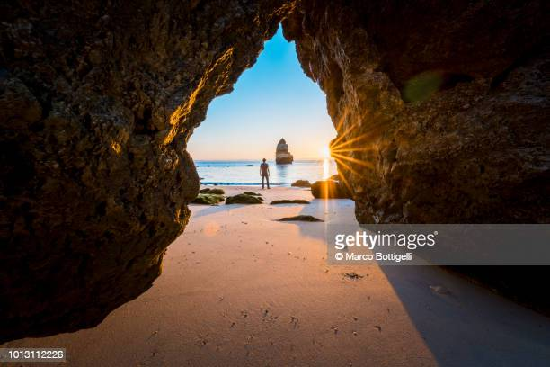 Man looking at view on the beach at sunrise, Algarve, Portugal
