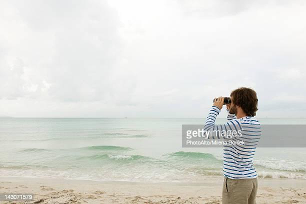 Man looking at view through binoculars