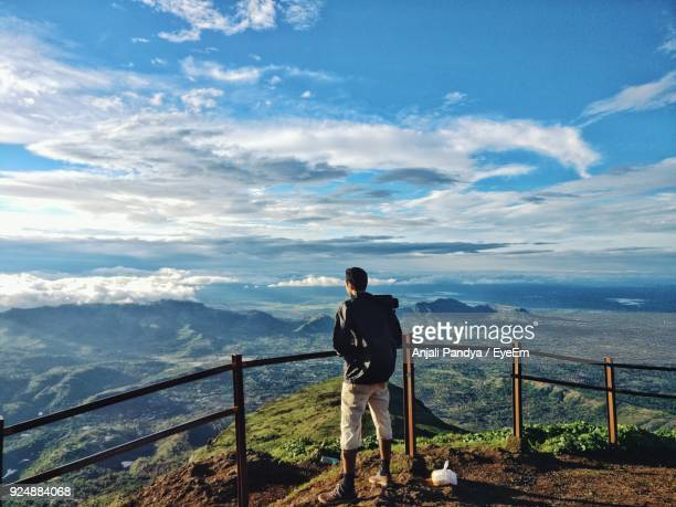 Man Looking At View While Standing By Railing Against Mountains And Cloudy Sky
