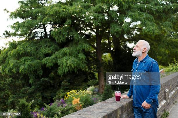 man looking at view with smoothie - hands in pockets stock pictures, royalty-free photos & images