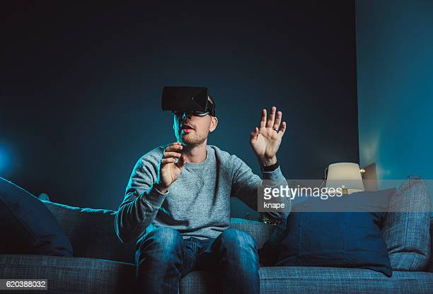 man looking at vr film with virtual reality glasses headset - gel effect lighting stock photos and pictures