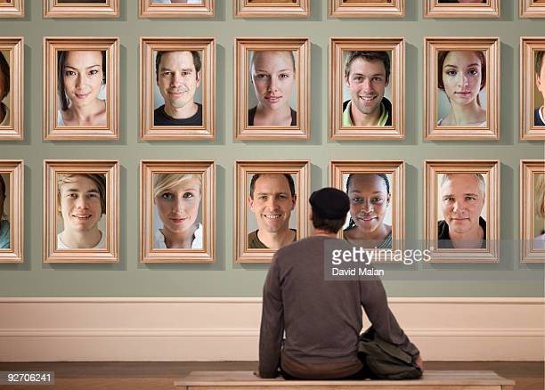 Man looking at wall of portraits in a gallery