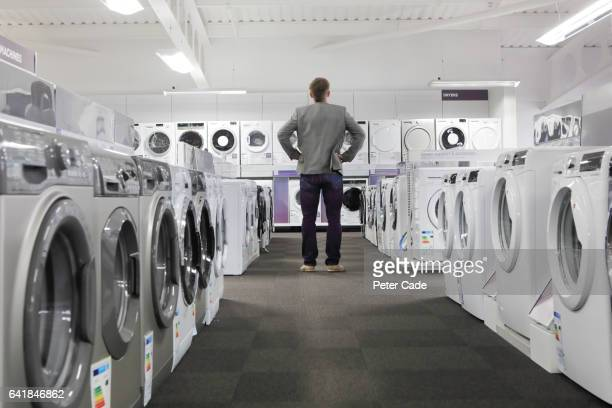 Man looking at washing machines and dryers in shop