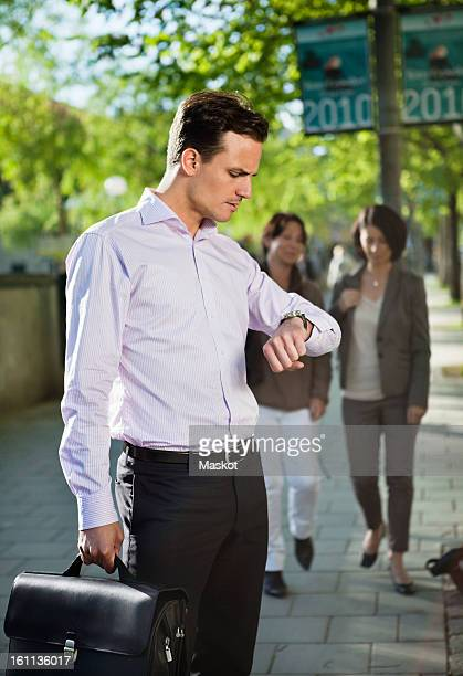 Man looking at watch with people in the background