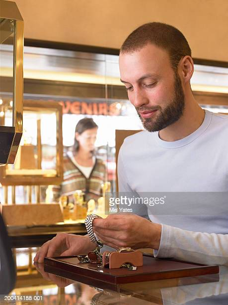 Man looking at watches on tray in jewellery shop, smiling