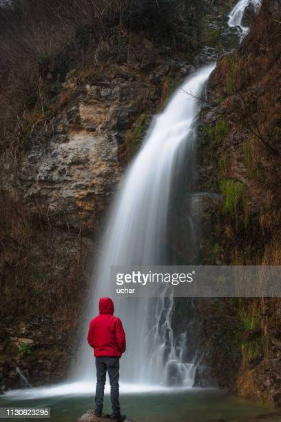 man  looking at waterfall - red jacket stock pictures, royalty-free photos & images