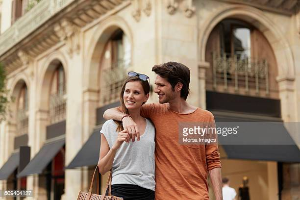 Man looking at woman against building
