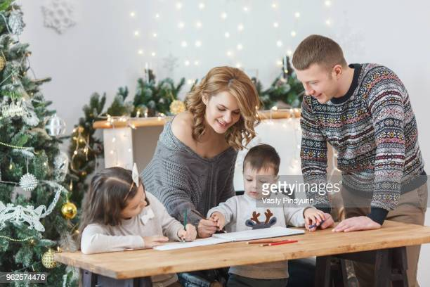 Man looking at woman and children drawing in book on table at home