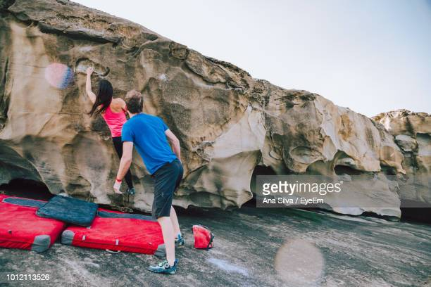 Man Looking At Woman Climbing On Rock At Beach Against Sky