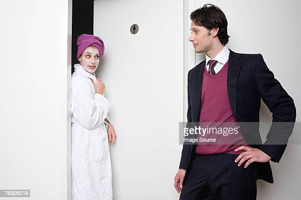 Man looking at woman coming out of bathroom