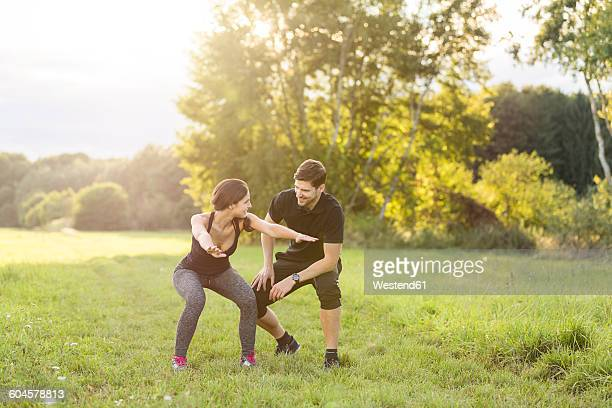 Man looking at woman doing knee bends in field