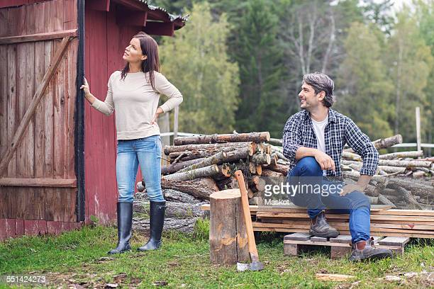 Man looking at woman holding open barn door while sitting by firewood