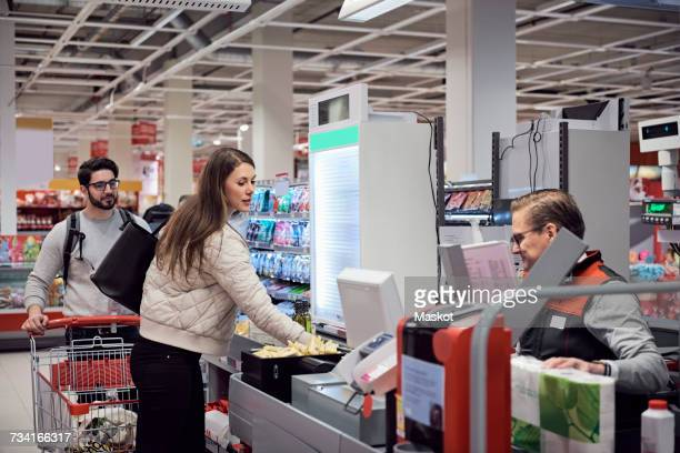 man looking at woman paying to mature cashier in supermarket - cash register stock pictures, royalty-free photos & images