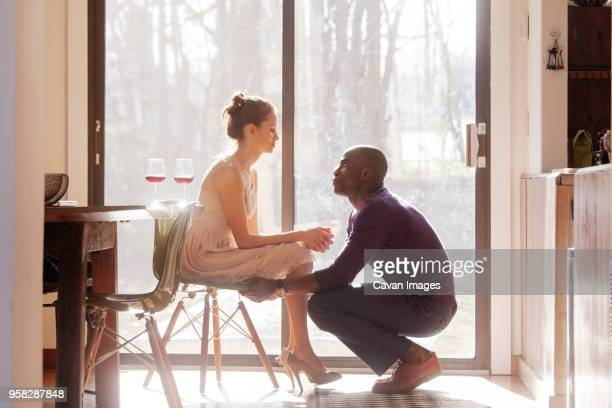 man looking at woman sitting on chair by window at home - woman sitting on man's lap stock pictures, royalty-free photos & images