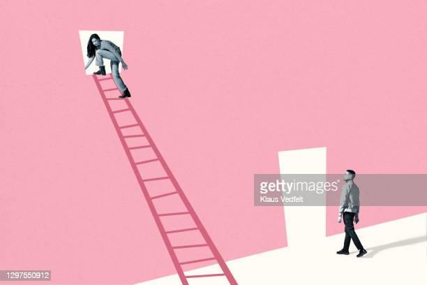 man looking at woman sneaking through pink window - ジェンダー・ステレオタイプ ストックフォトと画像
