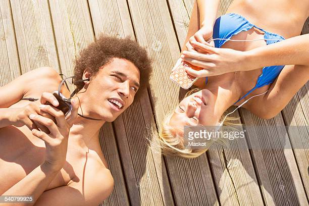 Man looking at woman using smartphone while lying on boardwalk