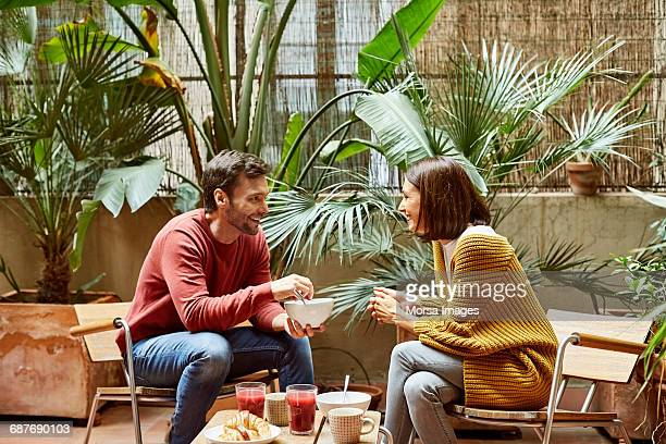 Man looking at woman while having breakfast