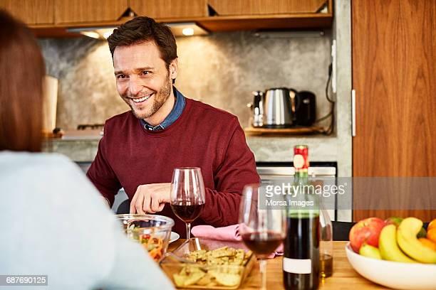 Man looking at woman while having food at home