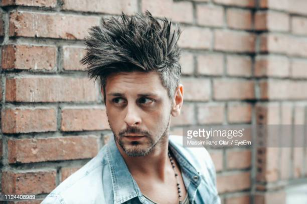 man looking away against brick wall - coiffure punk photos et images de collection