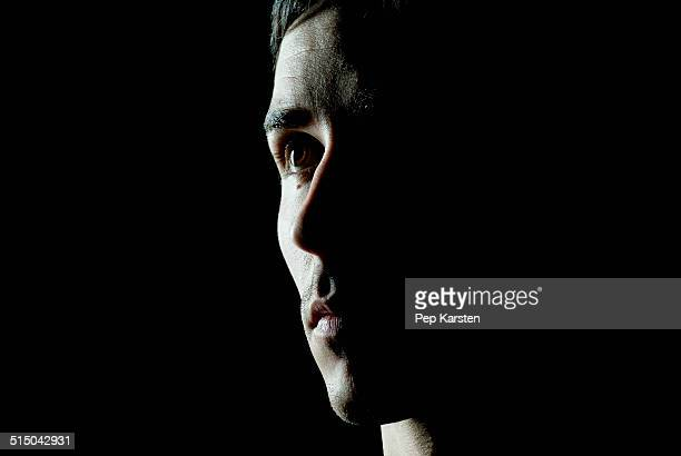 a man looking away contemplatively - shadow stock pictures, royalty-free photos & images