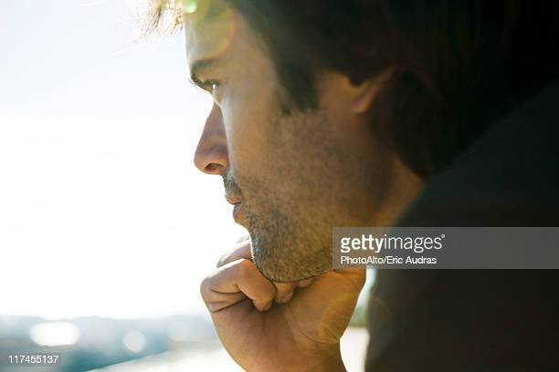 man looking away in thought, hand under chin - introspektion stock-fotos und bilder