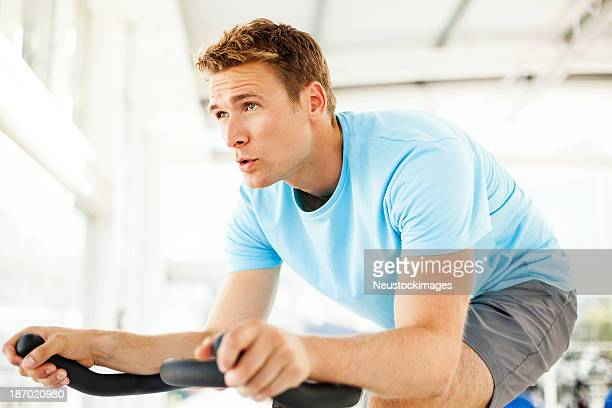 Man Looking Away While Cycling At Spin Class