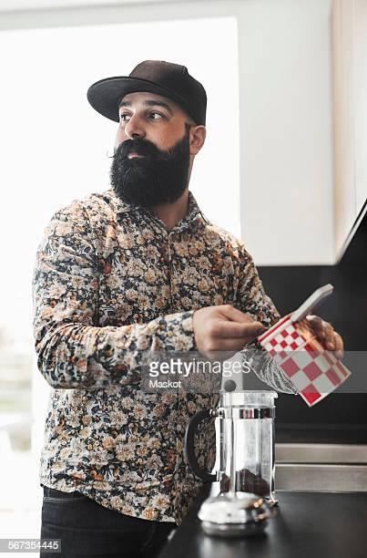 Man looking away while preparing coffee in kitchen