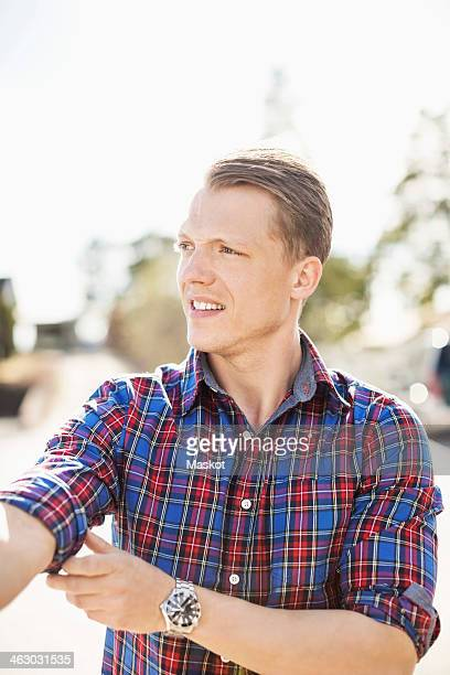 man looking away while rolling up shirt sleeve on a sunny day - long sleeved stock pictures, royalty-free photos & images
