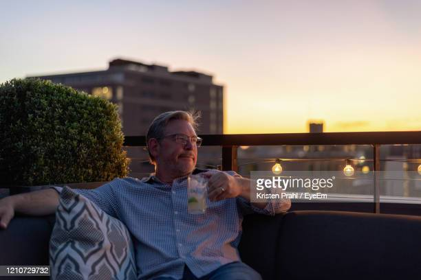 man looking away while sitting against sky during sunset - golden hour stock pictures, royalty-free photos & images