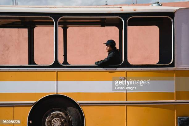 man looking away while sitting in bus seen through window - bus stock pictures, royalty-free photos & images