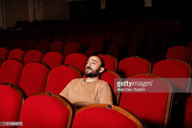 man looking away while sitting on chair in theater - solo un uomo foto e immagini stock