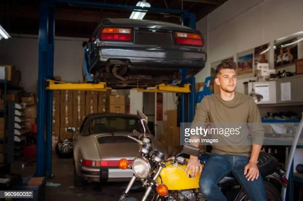 Man looking away while sitting on motorcycle in garage