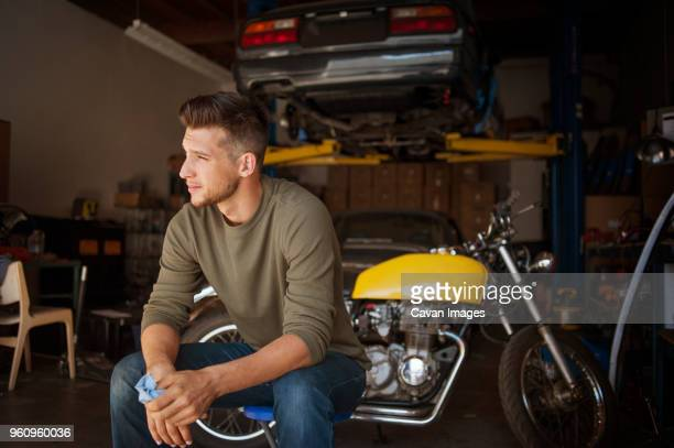 Man looking away while sitting on stool in garage