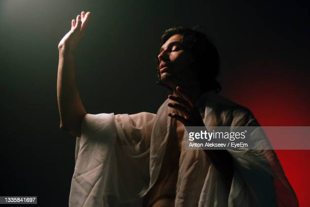 man looking away while standing against black background - singing stock pictures, royalty-free photos & images