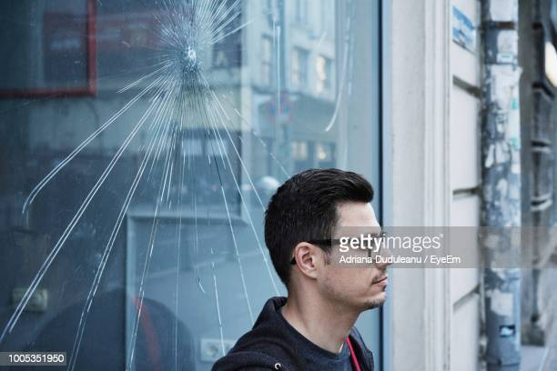 Man Looking Away While Standing By Cracked Window Glass