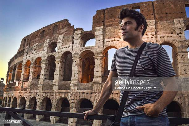 man looking away while standing by railing against coliseum - ancient civilization stock pictures, royalty-free photos & images