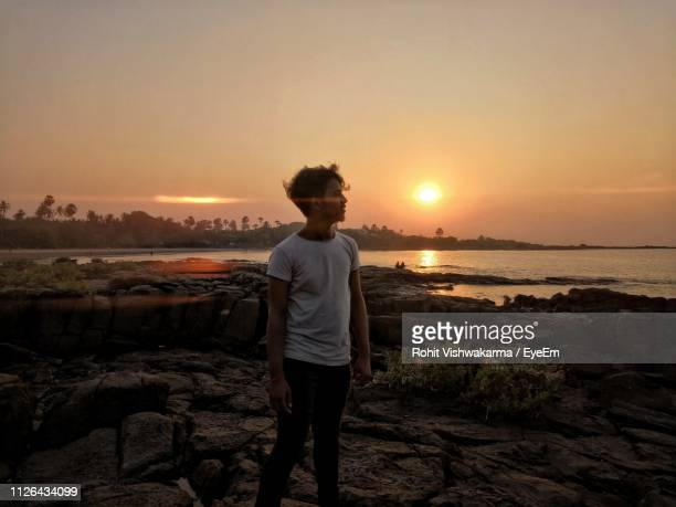 man looking away while standing on rock at beach against sky during sunset - sioux culture stock pictures, royalty-free photos & images