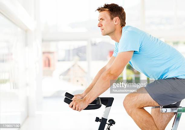 Man Looking Away While Training On Exercise Bike In Club
